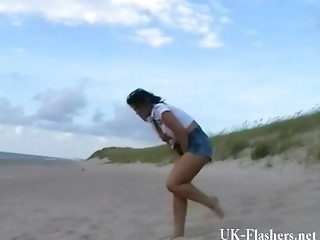 Exhibitionist beach babe flashing by the sea