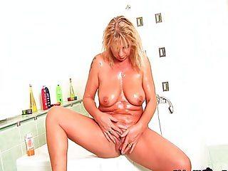 Chunky grandma with big tits rubs her clit