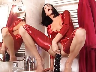 Lovely brunette, in red catsuit, plays with bigdildo in ass.