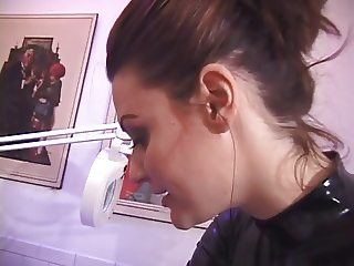 Brunette in corset, garters and stockings lets leather mistress paddle her ass