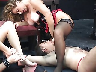 Two mistresses let their slaves suck on their feet, ass, and strap-ons.