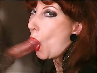 mature redhead wearing red lipstick and sucking cock