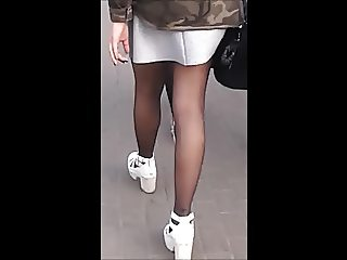 Girl with nice legs in mini skirt and black pantyhose