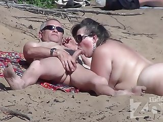 Blowjob on a nudist beach.