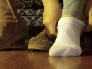 Woman puts her white socks back on after showing her bare feet