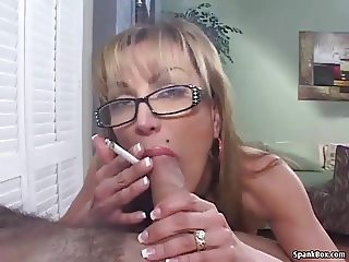 Mature smokes cigarette while sucking cock