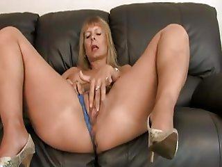 Mature blonde masturbates on sofa