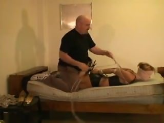 Girl hogtied, blind folded, and gagged on the bed