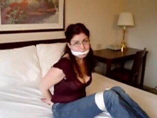 Redhead in jeans and glasses bound on the bed