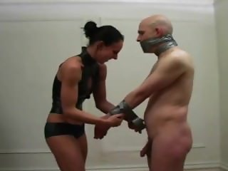 Naked man is bound and gagged with duct tape by sexy girl
