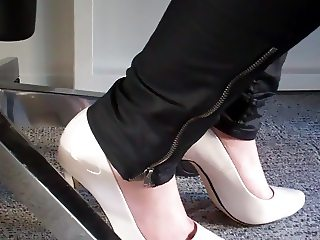 dangling again white high heels under desk